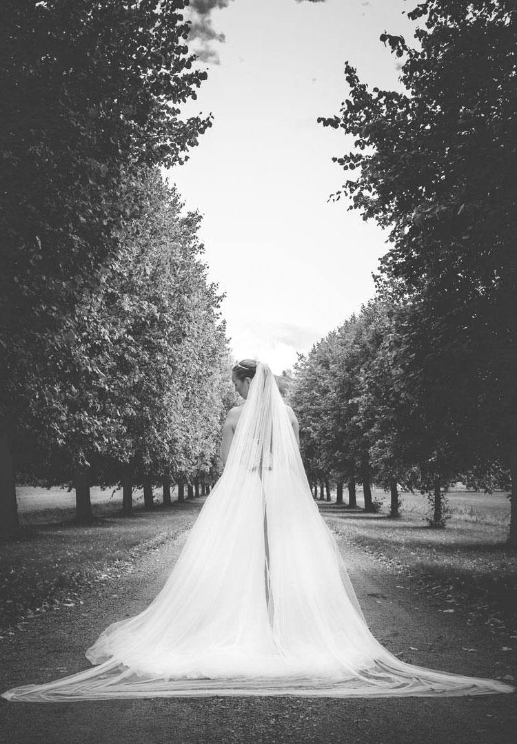 Bruden står i en Allè med store trær. Ryggen til oss.