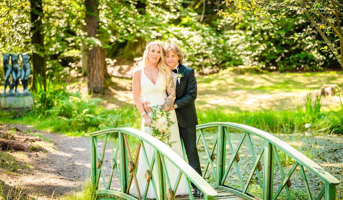 Bryllupsfotografering Brudeparet står på en liten bro over ett tjern
