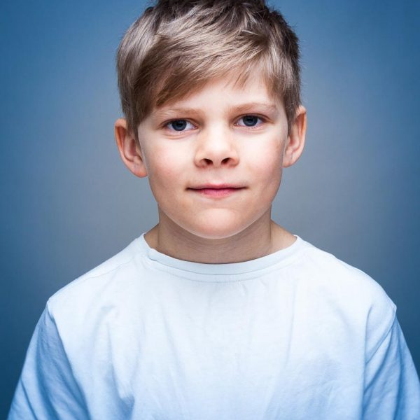 Portrett av en ung gutt med blå bakgrunn