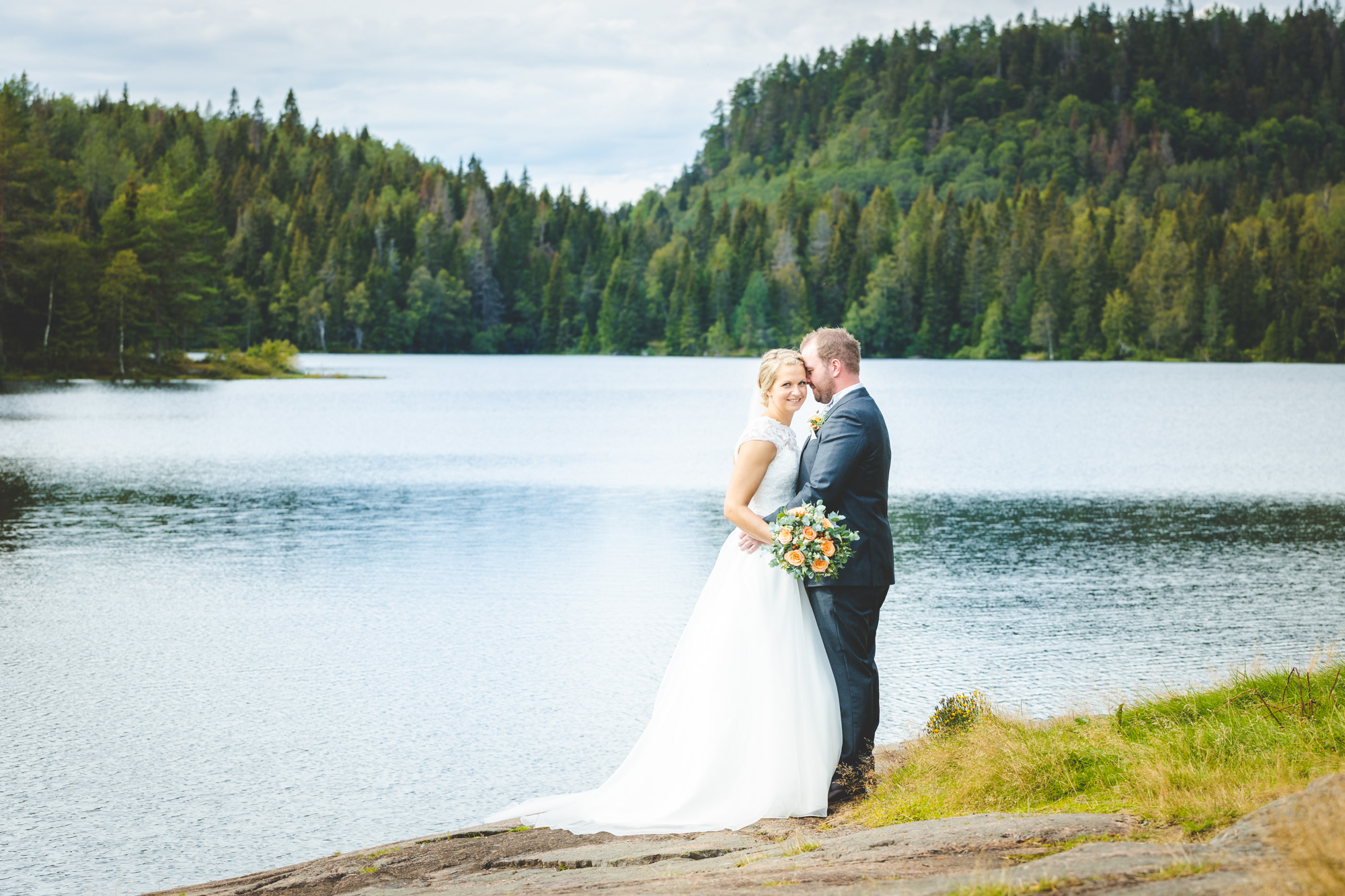 Bryllupsfotograf Tønsberg Brudepar står ved en liten innsjø
